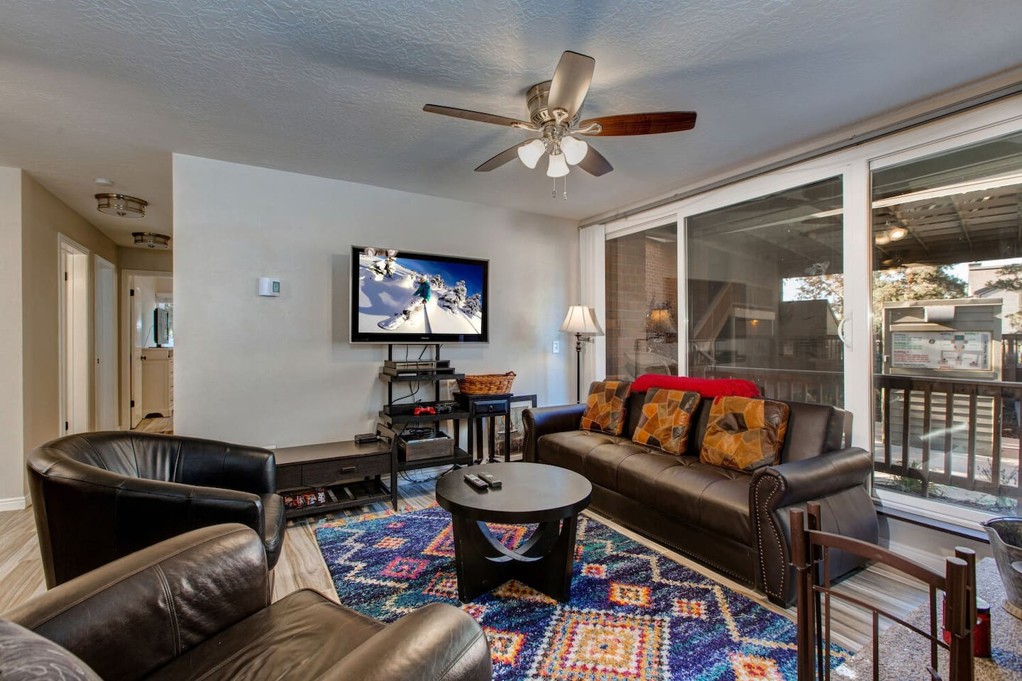 Living room with Smart TV, Leather Furnishings, Fireplace, and Private Balcony Access