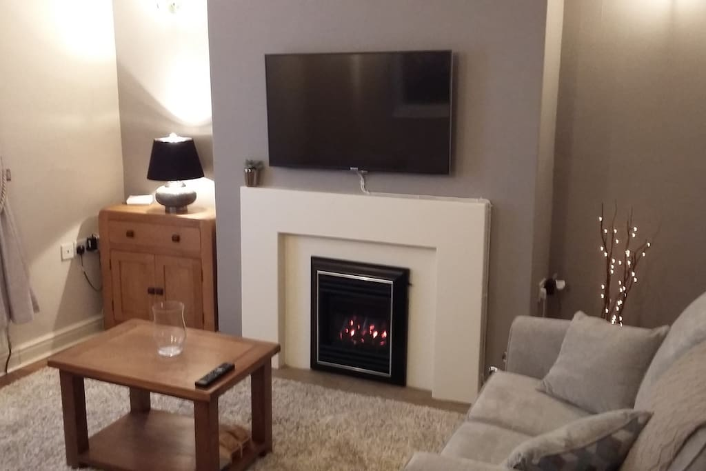 "Living room. Gas fire and 43"" 4K Ultra HD TV."
