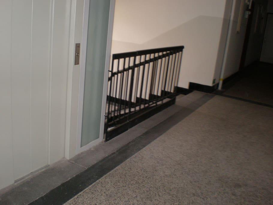 chodba domu s výtahem a částí schodiště-naproti výtahu je vchod do bytu.