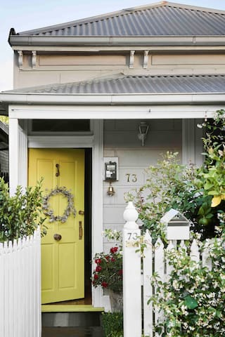 Vintage cottage circa 1890s with a bright yellow door to welcome you.