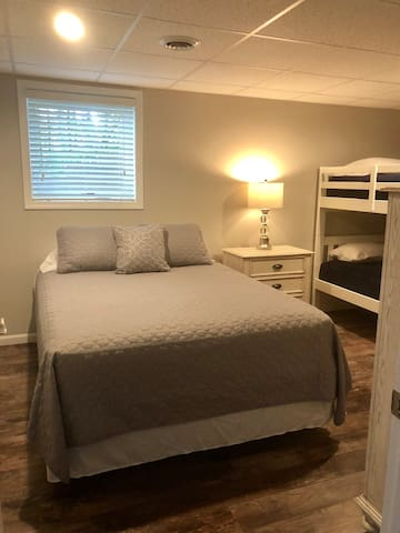 Lower level bedroom #2 with queen bed and twin bunk beds