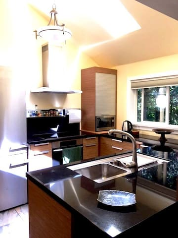 High end Miele appliances, granite countertops, sky lights and bar seating complete this beautiful cooking space.