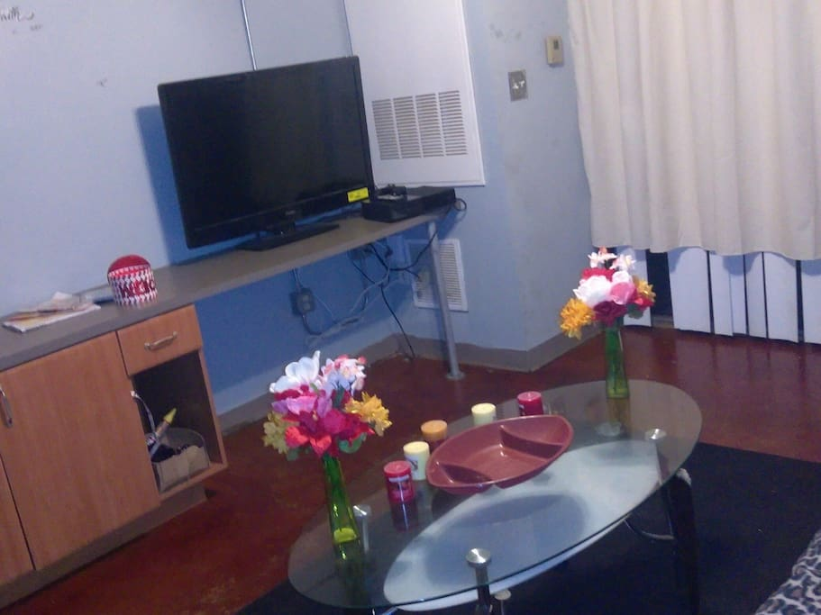 television with cable table with candles and flowers.