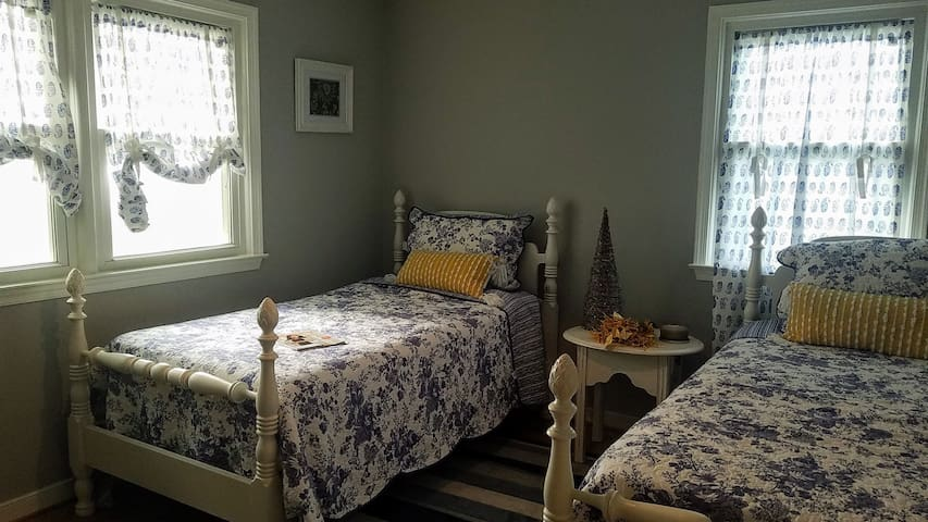 Bedroom #3 The Rustic Marigold features a rocking chair, set of twin beds, chest, and closet.