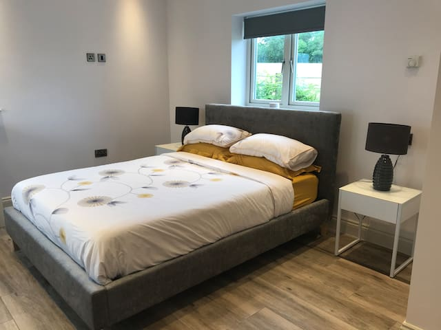 Contemporary furnished bedroom with a king sized bed, wardrobe, chest of drawers and a tall table and chairs.