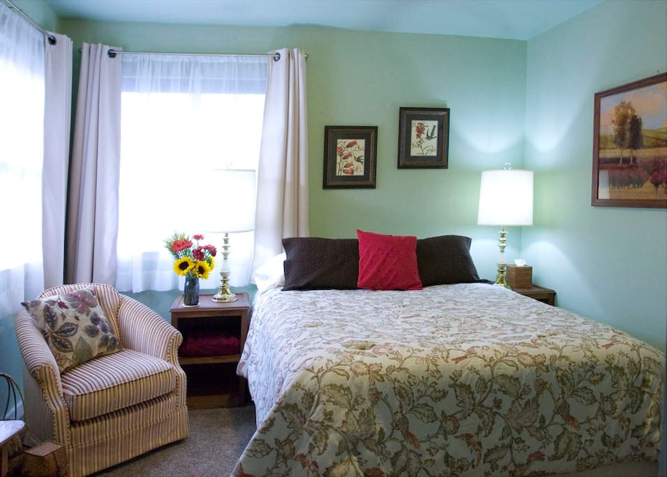 Green Room is perched over the southeast corner and drenched in a morning sunshine. A small collection of my Grandma Bertha's hats and purses are displayed above her oak vanity. It has a queen-sized bed with support foam that gently contours the body for a terrific night of sleep. The Green Room shares a bathroom with the room next door.