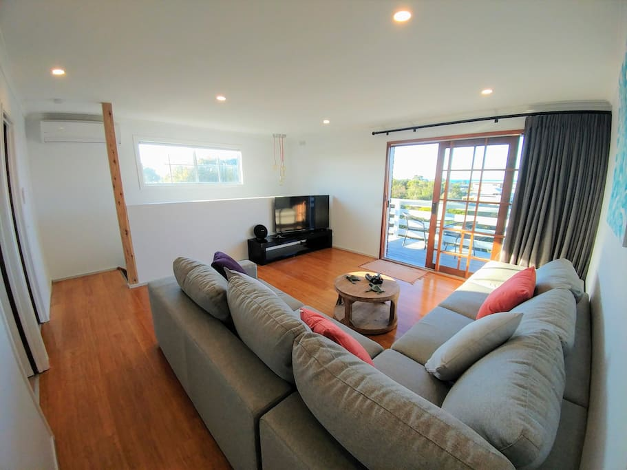 """Upstairs lounge with 55"""" TV, access to the balcony and water views."""