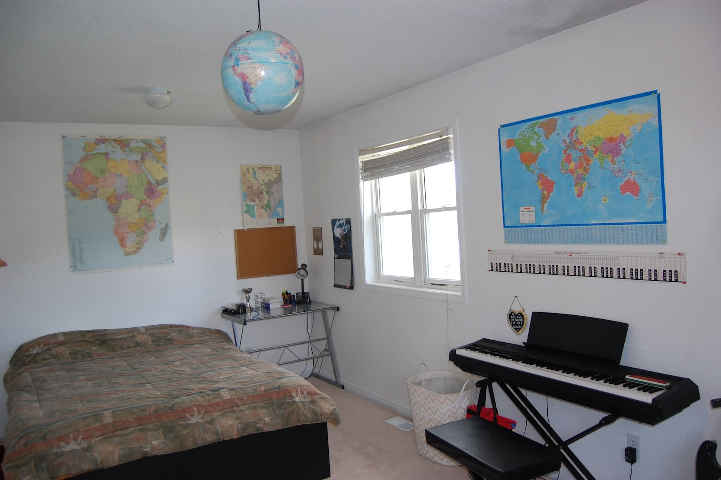 """Spacious bedroom on second floor with queen-sized bed, ample closet space for 2, reading desk, love-seat sofa, an electric piano and guitars for entertainment with an option for a 32"""" TV upon request."""