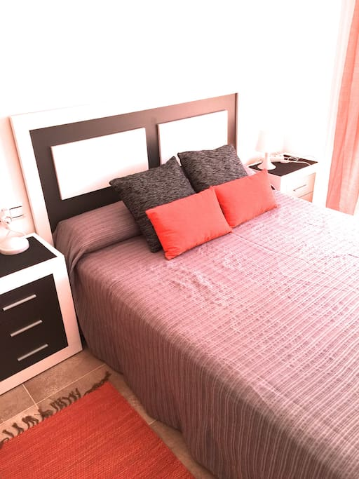 Dormitorio de matrimonio con cama de 1,50 de colchón de gran confort, con baño y terraza exterior que da a jardín. Maravillosas puestas de sol desde la terraza.