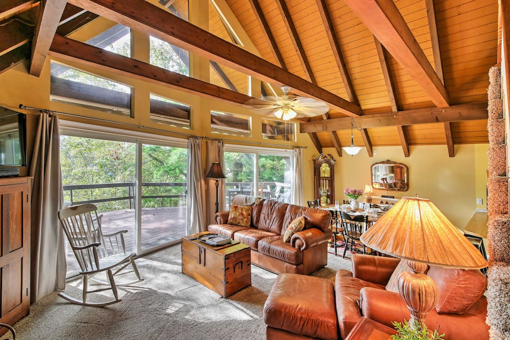 The interior of the home boasts, cathedral ceilings, beautiful wood beams, and floor-to-ceiling windows.