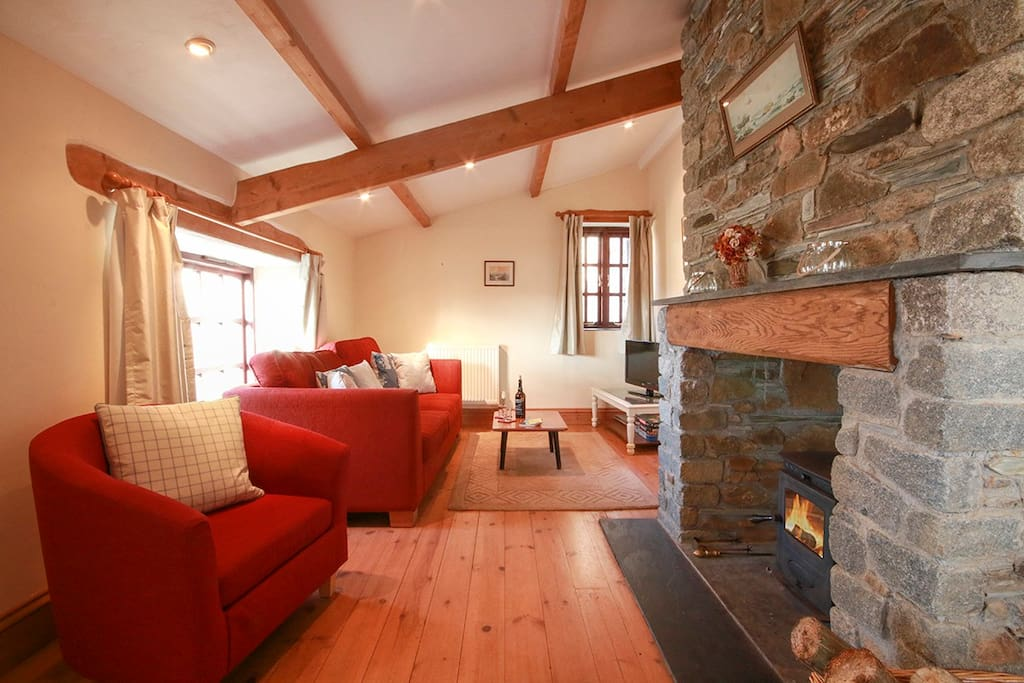 Open plan but cosy living room area with woodburning stove, traditional stone and beams