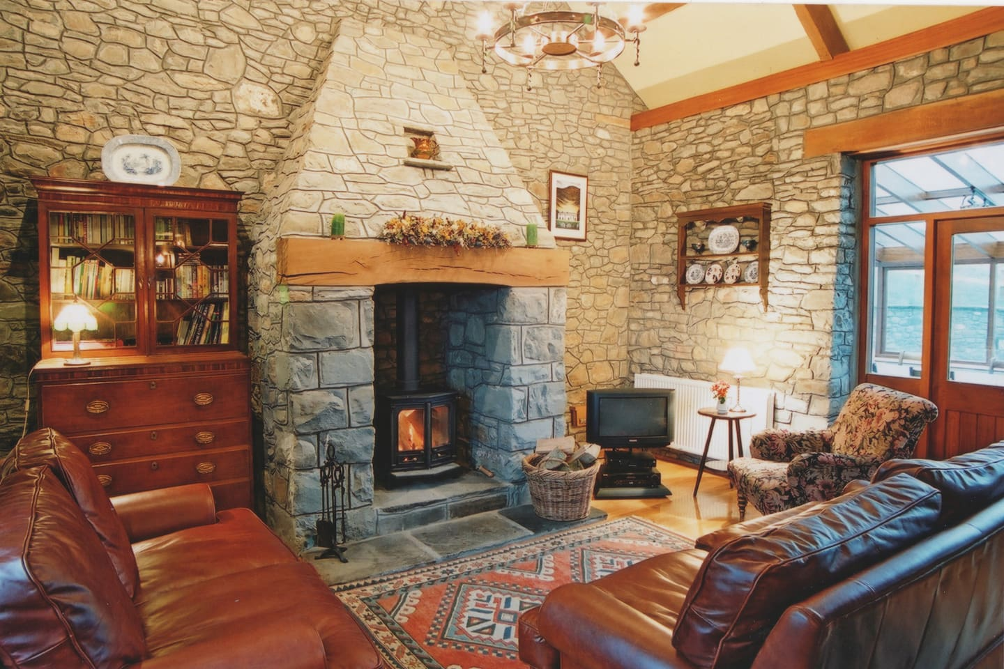 A Living Room full of character and a cosy log fire.