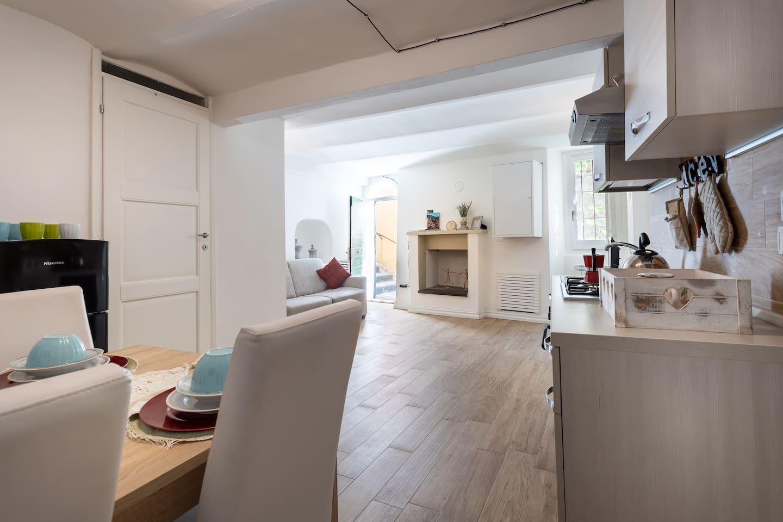 Ampio soggiorno con divano e camino e ampia cucina