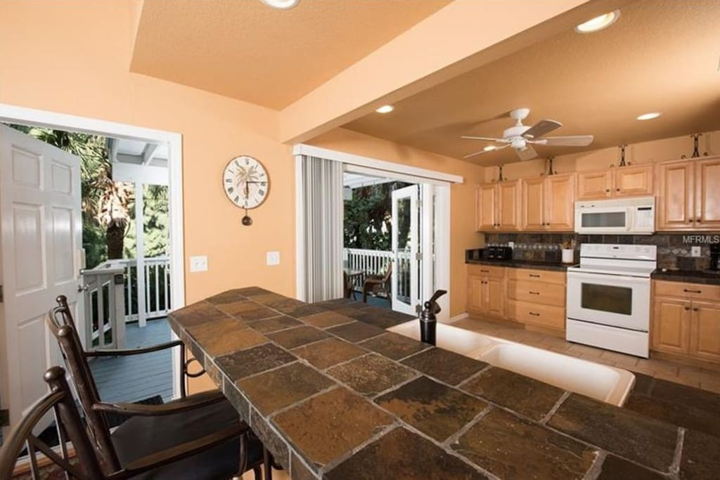 Full Kitchen walks right out onto the lush porch