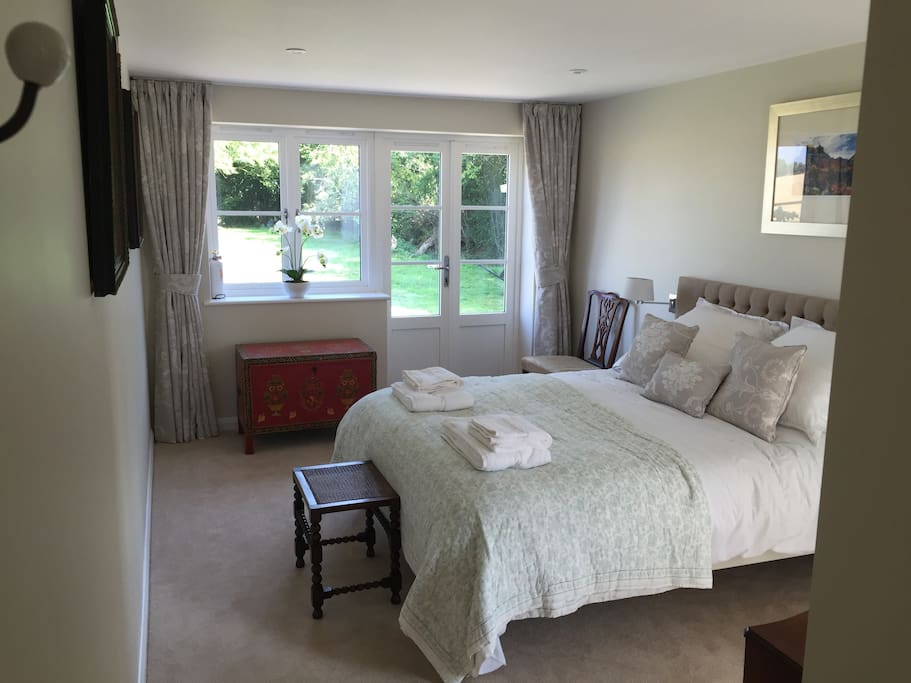 King size bedroom with en suite French doors give access to the patio and garden with table and chairs.
