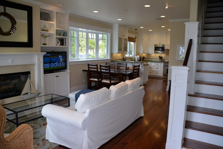 The main entry opens up into the open floor plan living room that includes a flat screen TV and large wood burning fireplace.