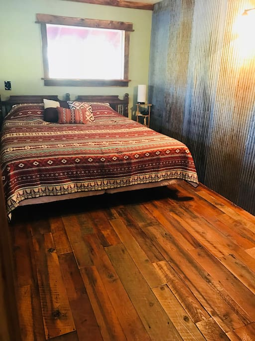 This first bedroom has a very comfortable King Size bed, bedroom wall heater, a sliding barn door, and seating.