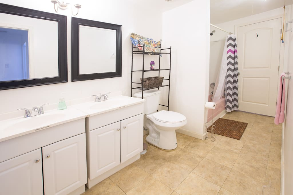 Access to a spacious shared bathroom with double vanity.