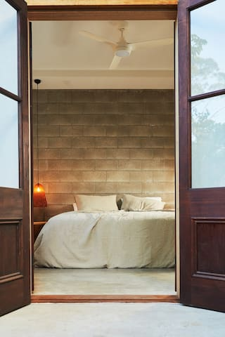 French doors, king bed, luscious linen Downstairs bedroom opens up onto private courtyard