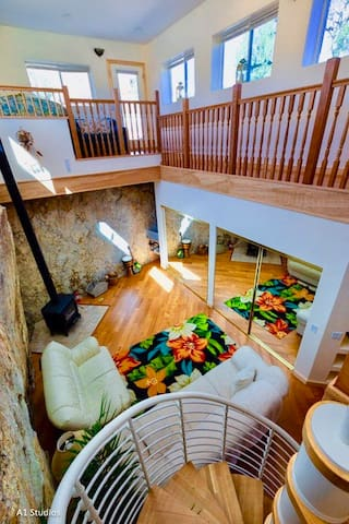 The Cave & Loft from the Spiral Staircase. Feel free to light the wood stove on cool nights. Enjoy the softness & warmth of the radiant heated wood floors. A drop down 9' screen lives below that beam. Enjoy touching the natural Granite Cliff walls.