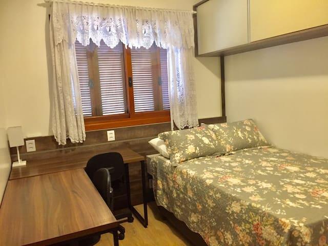 Quarto de casal, com escrivaninhas para estudo ou trabalho, ar condicionado split e armários.