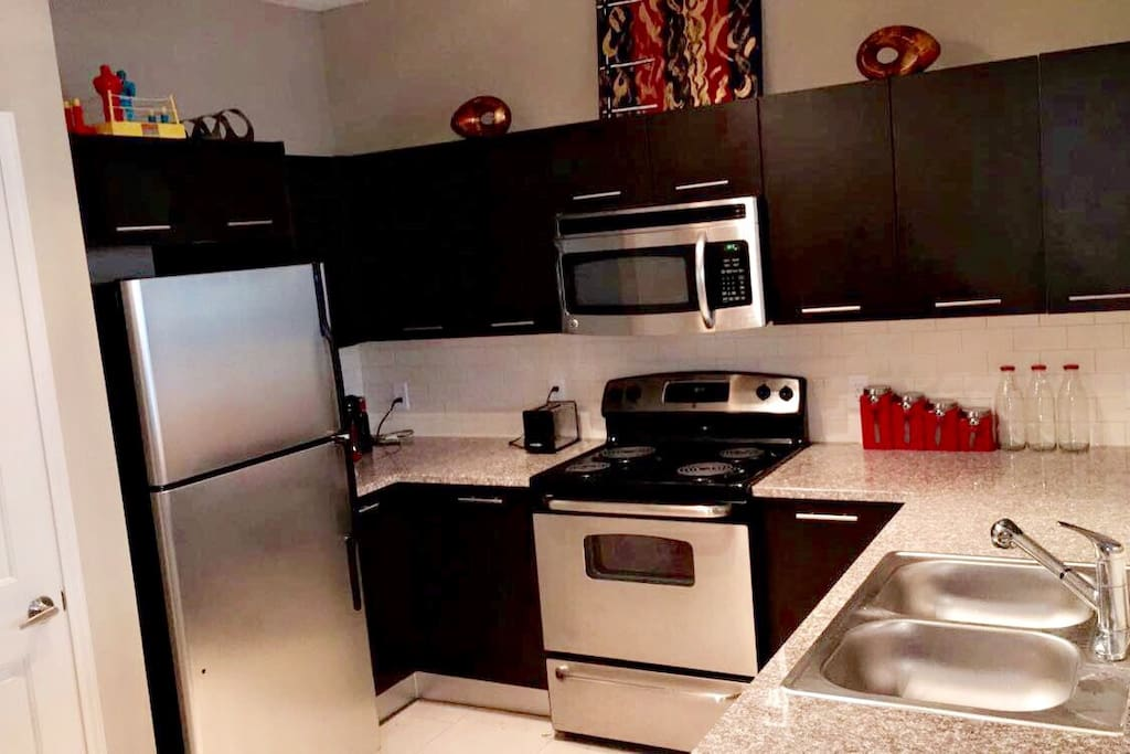 Kitchen - Microwave, Oven, Refrigerator, Dishes, Utensils, and Cookware.