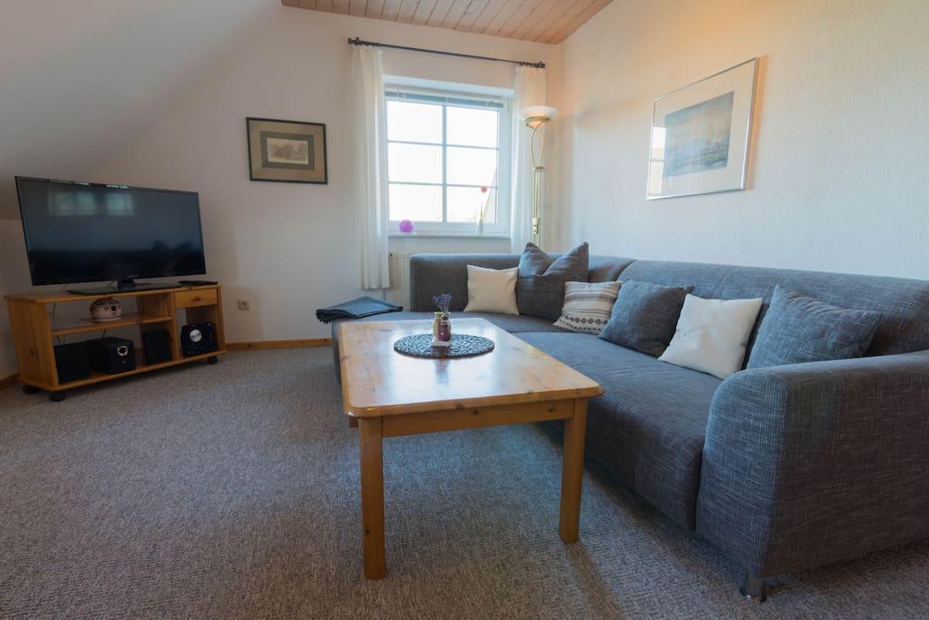 Wohnzimmer mit gemütlicher Couch, Essecke, SAT-TV und Stereoanlage