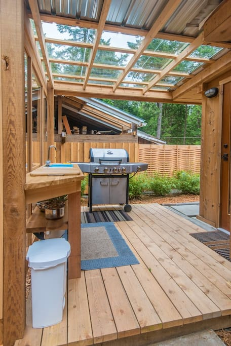 An outdoor cooking area includes a BBQ.