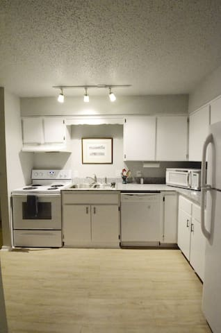 Kitchen with oven, microwave, dishwasher and full size fridge