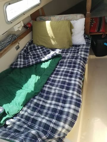 "Optional sleeping area with more headroom than the v-berth -- dining table drops down to make a bed slightly wider than a twin bed, that's 6ft. long.   Works diagonally for someone 6'3"".  For a couple in that spot the bed is ""half-full"".  V-berth is plenty comfy for two."