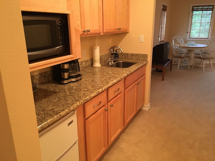 Microwave, mini-fridge, coffee maker, kitchen sink, dishes.