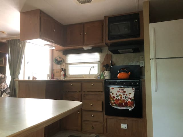 Full size frig and hot water heater.three burner stove with oven. Counter , bar space.