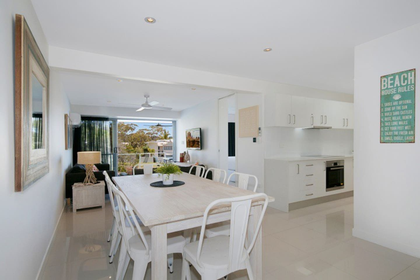 Open plan kitchen, dining and lounge areas with sliding doors opening up to spacious balcony with Noosa River and sunset views