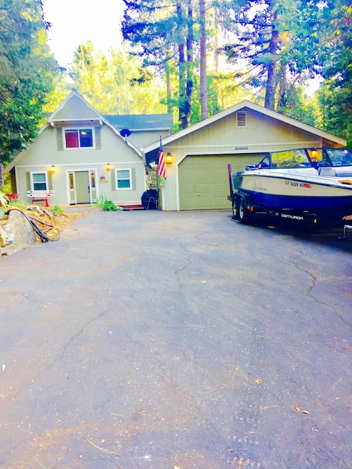 The front of the Boat ramp house at Scotts flat lake with a large driveway, picnic table, hammock, a large deck, BBQ, a fire pit, and great out door lighting.