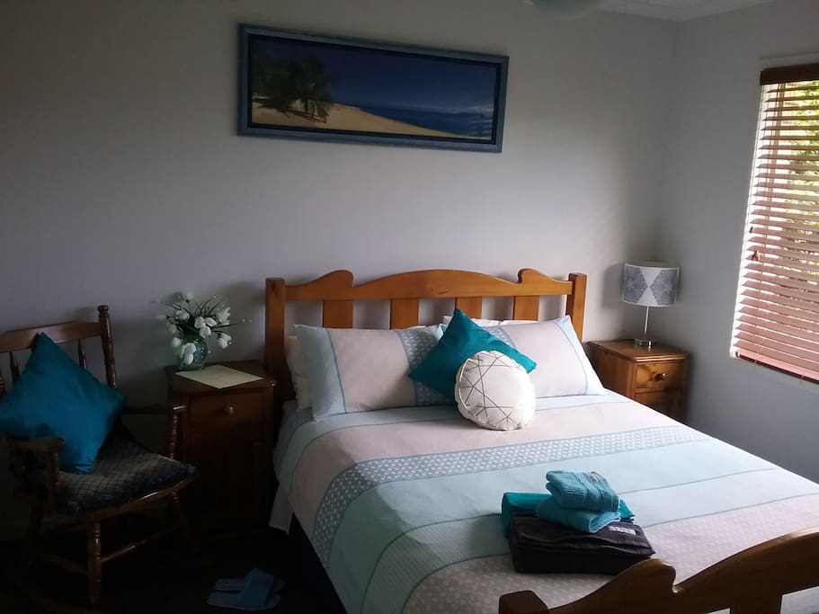 Main Guest Bedroom. Large room with Ceiling Fan, Large Window, Blind, Queen Size Bed complete with Clean Sheets, Blanket, Dooner, Pillows, Towels. Hanging Space, Bedsides & Lamp, Rocking Chair. Suitable for Couples  or Single Traveller. This room over looks the Back Yard.