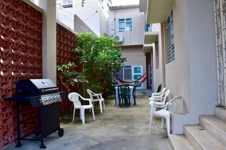 Patio with BBQ, chairs, domino table, dominos, hammocks, beach chairs, cooler, volleyball and beach toys.