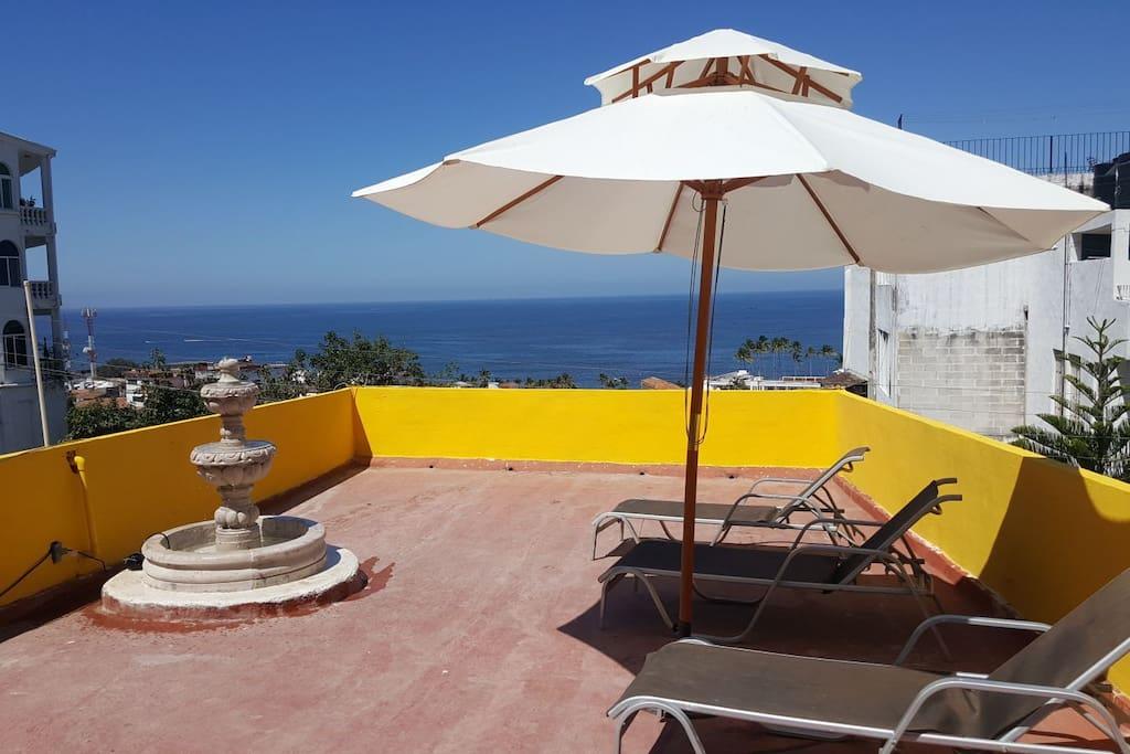 Terraza con vista al mar: Sillas acapulco, camastros, fuente, sombrilla, rincón de lectura, etc.