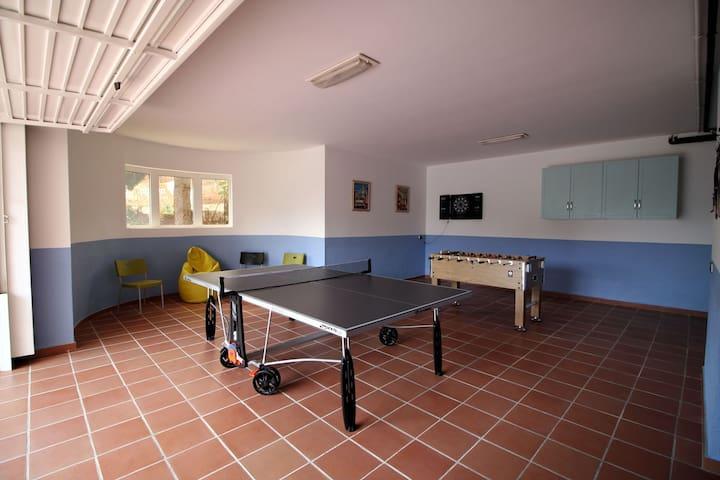 Zona ocio con mesa de ping pong, futbolín y diana de dardos / Leisure area with a tennins table, a football table and a dard board