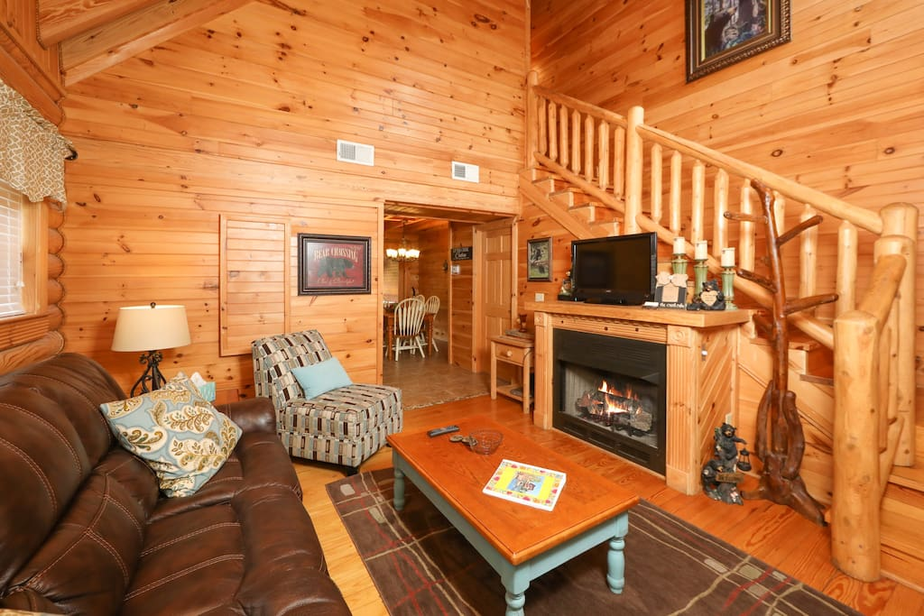 Cheerful wood-paneled walls and fireplace in the main living area. Professional housekeeping services provided by TurnKey.