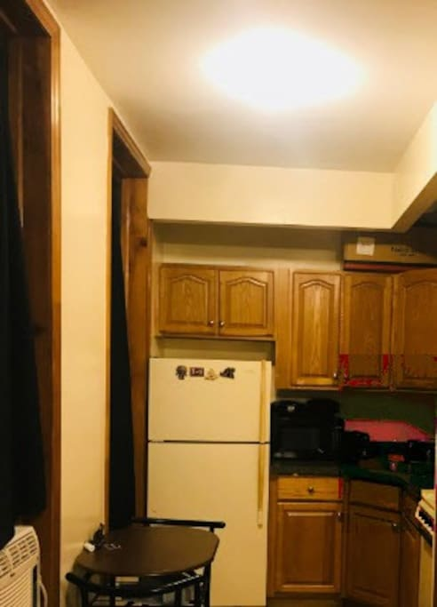 Eat in kitchen with dining table for two, coffee grinder, coffee maker, microwave etc.