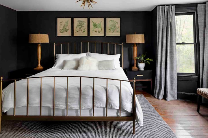 The master bedroom has sultry dark walls with a brass bed made with luxurious Restoration Hardware bedding.  The bedroom also has a dresser and a tv.