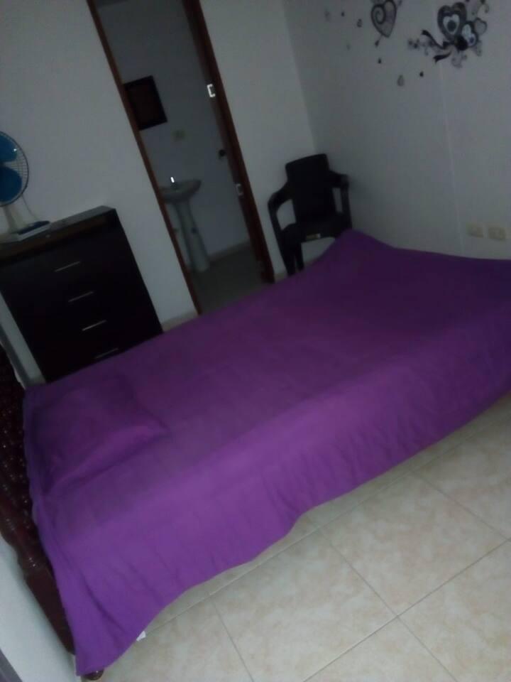 cama doble con tendido, comoda para la ropa y ventilador.