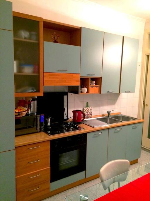 cucina attrezzata con frigorifero, forno, microonde, bollitore, macchina da caffè