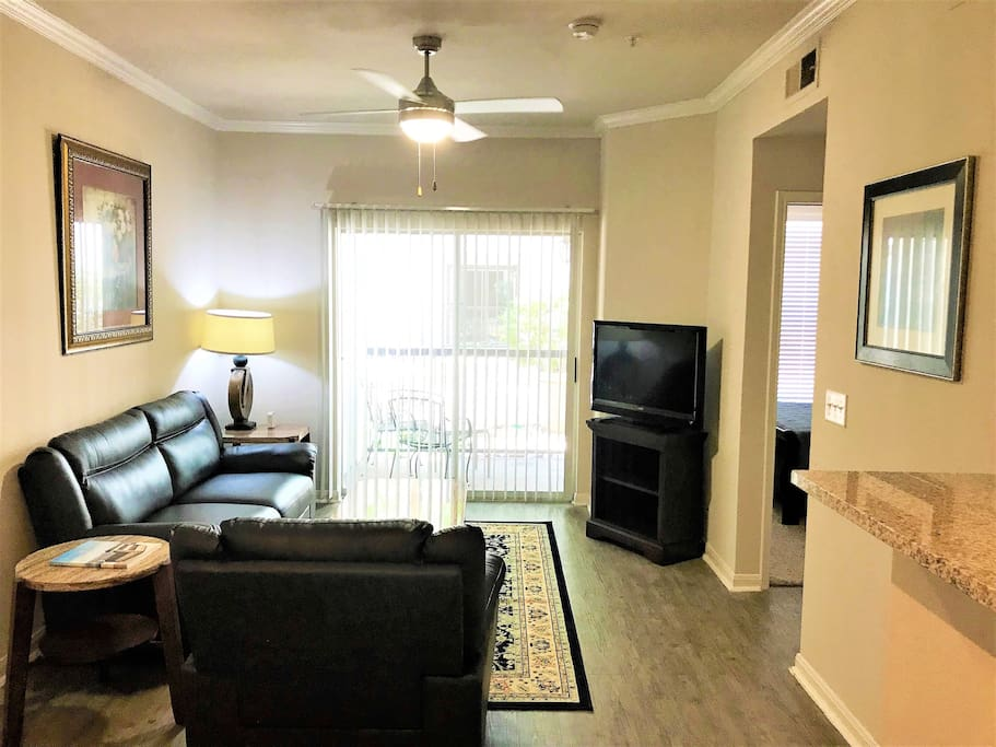 Living Room-Very spacious & includes TV with Netflix, AmazonTV, live TV & all movie channels (HBO, etc) via ATT App. New full-size comfy leather couch, sofa chair, & high speed 50mbps Wifi. Personal outdoor patio access with outdoor table and seating