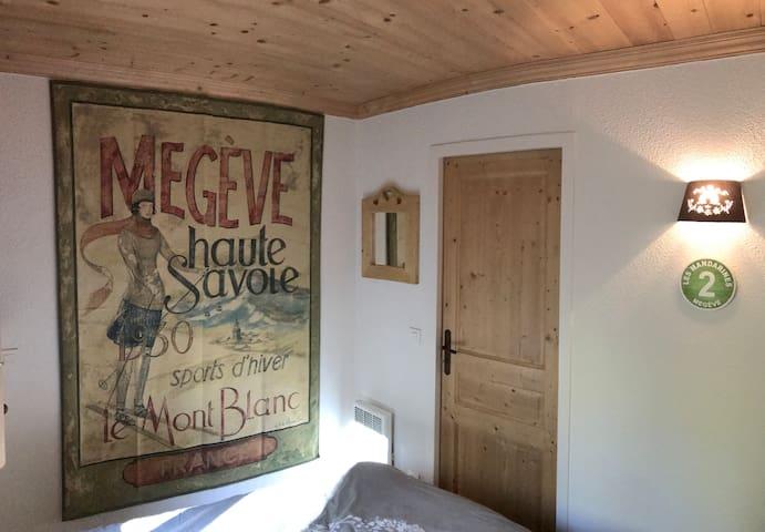 Chambre avec lit double - tapisserie Megève et ambiance bois. Chambre lumineuse avec fenêtre ouvrant sur le jardin (avec volets intérieurs et extérieurs).