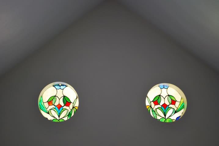 Colored glass windows in suite lets in pretty colored light.