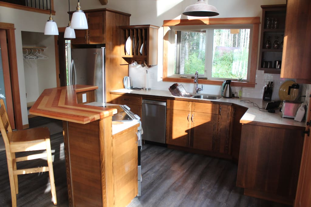 Beautiful wood bar overlooking kitchen with pots and pans. For yummy breakfasts and such.