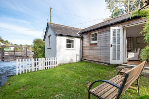 A small and cosy former artist shack by the river with everything you need, which makes a great base for couples and small families