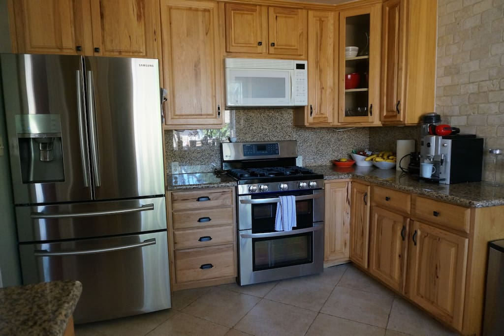Kitchen with double oven, microwave, espresso machine, refrigerator that dispenses sparkling water, and dishwasher.