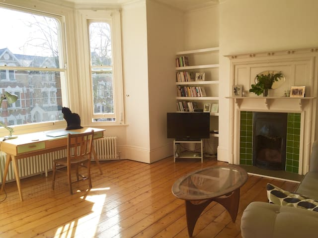 Bright, spacious lounge with bay windows overlooking the tree-lined street.